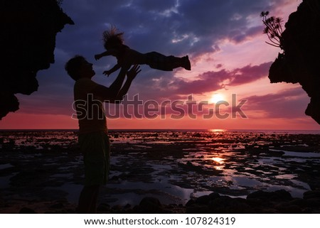 Dad having fun with his son in the sunset - stock photo