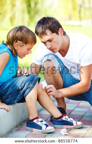 Dad helping boy to wipe blood off his injured leg - stock photo