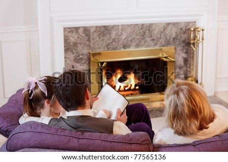 Dad helps his daughter with reading while her mother watches - stock photo