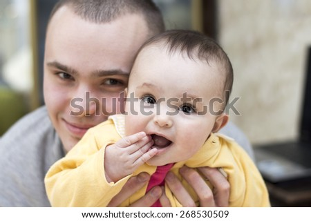 Dad holding his little daughter having fun together - stock photo