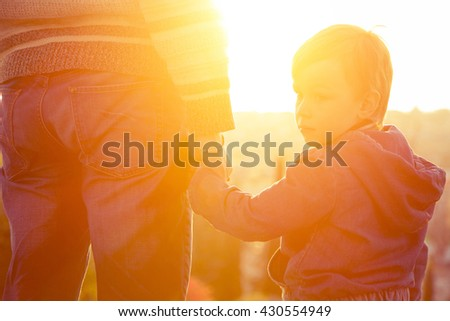 Dad holding the hand of his son, and he looks back and look sad. Family composition - stock photo