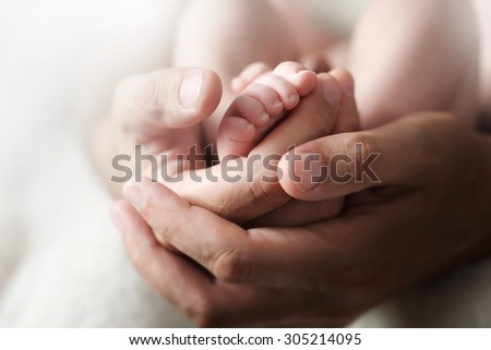 Dad holds in his hands a small baby foots