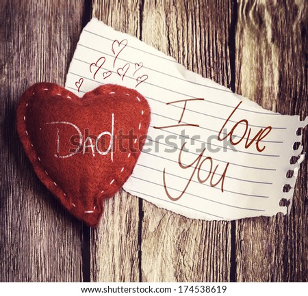 Dad I Love You written on a peace of paper and a heart on a wooden background - stock photo