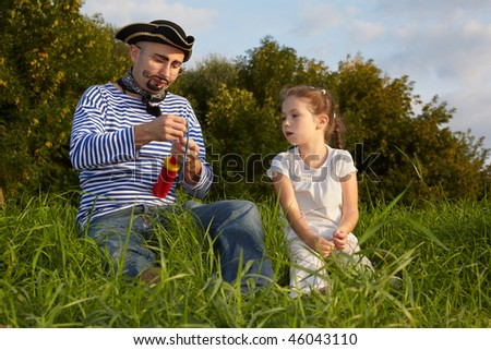 dad in pirate suit and daughter is sitting on grass. dad get ready to inflate air-balloon - stock photo