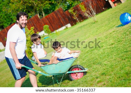 Dad in white driving boys on the wheelbarrow