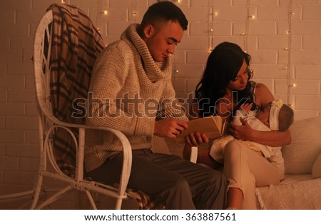 Dad is reading a book to a daughter, mother cradles her in his arms - stock photo