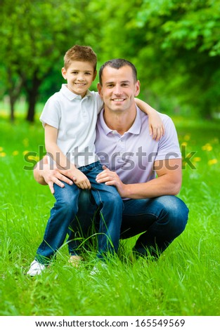 Dad keeps son on the knee in the park. Concept of happy family relations and carefree leisure time - stock photo