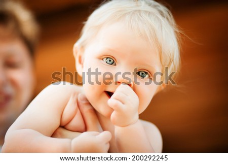Dad leaned child, the child with blue eyes holds her hand in her mouth - stock photo