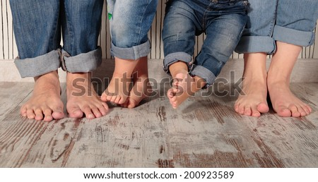 dad, mom and daughters barefoot in jeans - stock photo