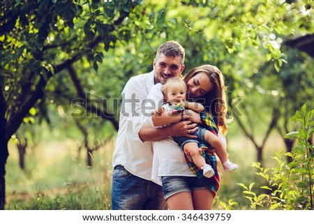 dad, mom and little girl on the farm on a background of trees - stock photo