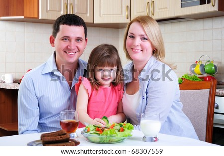 Dad, Mom and their little daughter lunching together in his kitchen. - stock photo