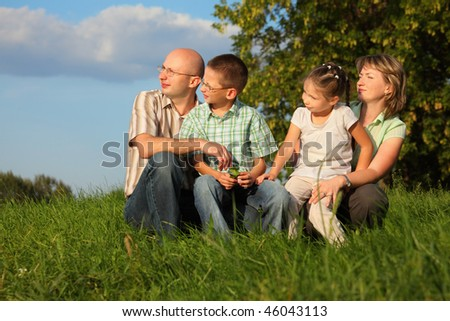 dad, mom, son and daughter in early fall park. they sitting on grass and looking at sunset - stock photo