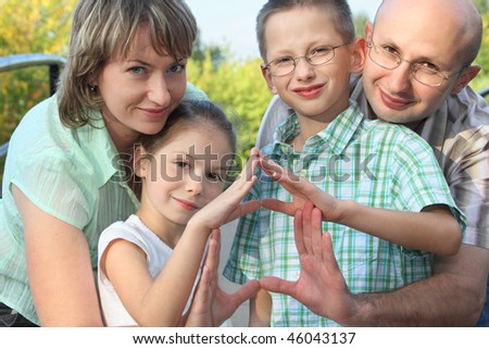 dad, mom, son and daughter is using their hands to represent home. focus on son's face. - stock photo