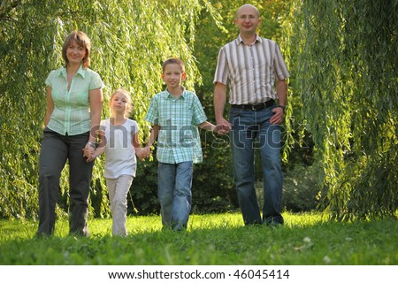 dad, mom, son and daughter is walking in early fall park. - stock photo