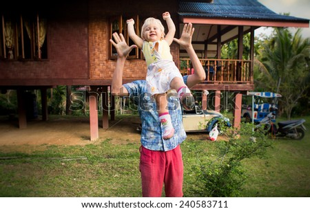 dad play with his blonde baby daughter drop off her in the sky  - stock photo