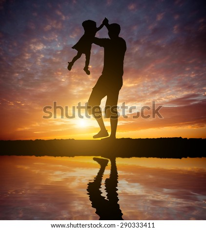 Dad playing with baby daughter on the beach at sunset. Silhouette photo - stock photo
