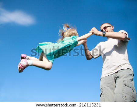 Dad playing with his baby daughter in a blue dress, he turns her around himself at arm's length, selective focus, the effect of motion - stock photo