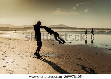 Dad playing with his daughter on the beach at sunset - stock photo