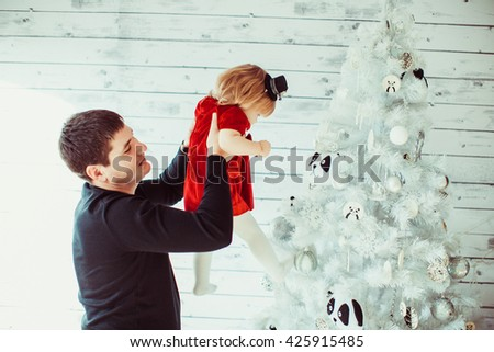 Dad plays with daughter near Christmas tree - stock photo