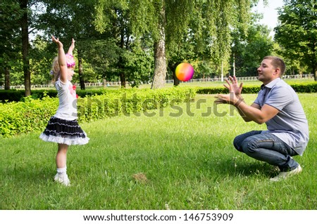 dad plays with her daughter with the ball on the nature - stock photo