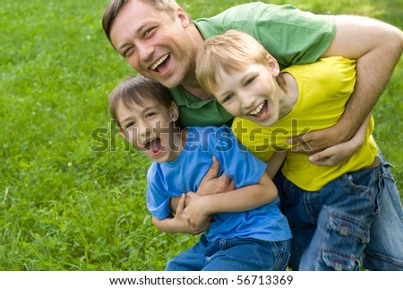Dad plays with young children outdoors - stock photo