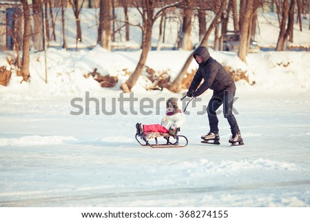 dad skate child on a sled