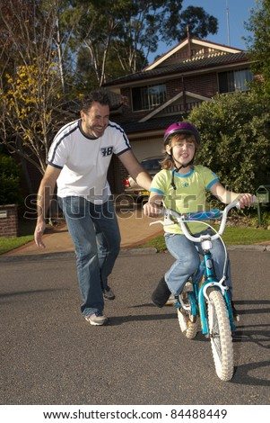Dad teaching his daughter to ride a bike - stock photo