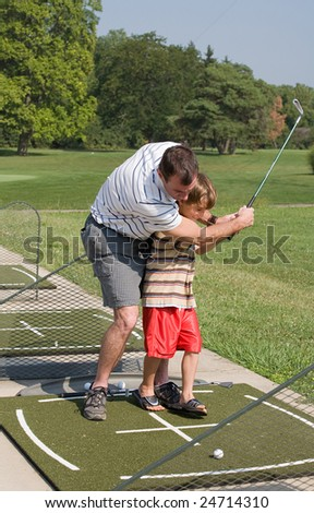 Dad Teaching Son Golf - stock photo