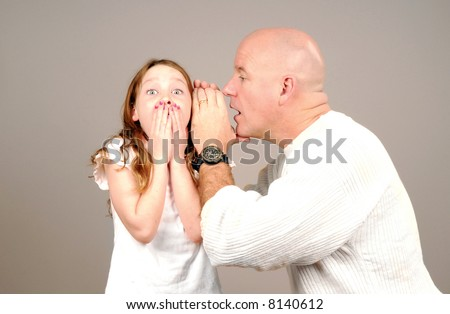 Dad Telling Daughter a Secret that Surprises Her - stock photo