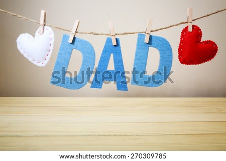 DAD text and felt hearts with stitches hanging on a string - stock photo