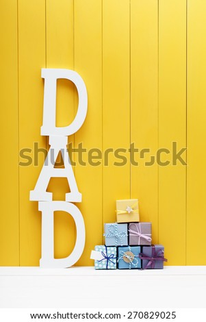 DAD text letters with little gift boxes on yellow wooden background - stock photo
