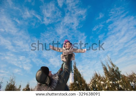 Dad throws up baby daughter in winter against the blue sky, lifestyle, winter holidays - stock photo