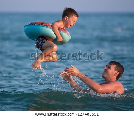 Dad throws up his son in an inflatable circle in the sea - stock photo