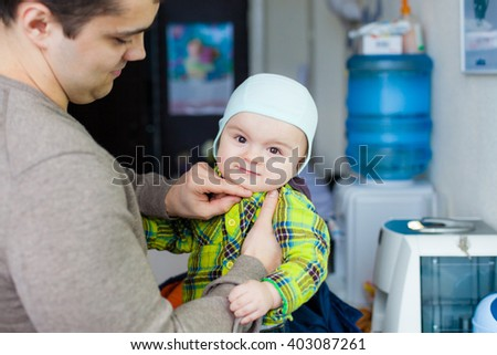 Dad ties hat to his son. Little baby makes faces at the background of water cooler, closeup  - stock photo