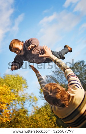 dad tosses son into the air in an autumn Park. Happy family. - stock photo