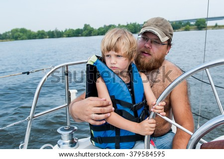Dad with a boy sailing on yacht