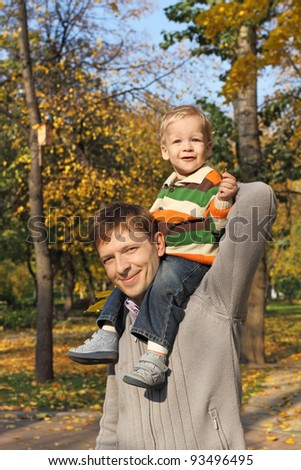 Dad with a child on the shoulders of the walks in the park