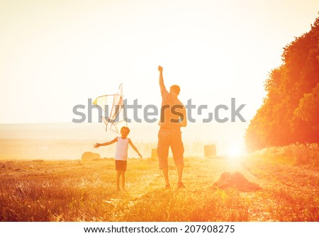Dad with his little daughter let a kite in a field - stock photo