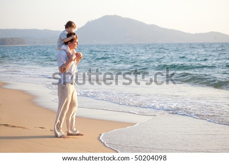 dad with his little son on his shoulders enjoying sunset - stock photo