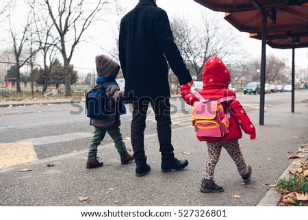 Dad with kids going to the bus stop