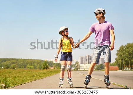 Dad with little daughter on the skates. two people rollerblade. sports family rollerskating outdoor - stock photo
