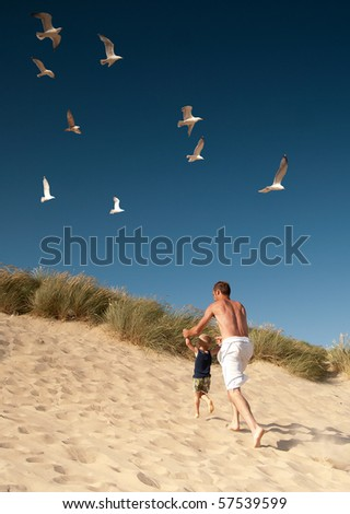 dad with son on the beach - stock photo