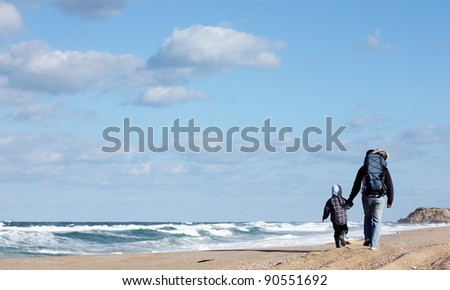 Dad with son walking on a winter beach - stock photo