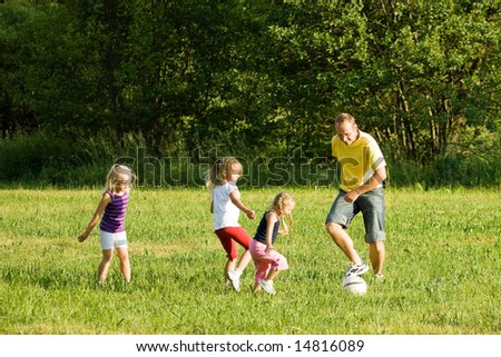 Dad with tree daughters playing football (well, soccer for North America) on a green, sunlit meadow - stock photo