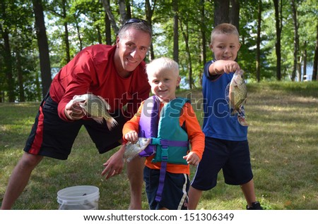 dad with  young sons and the fish they caught fishing - stock photo