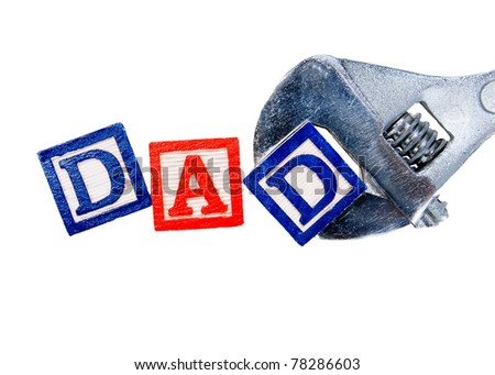 Dad written in colorful blocks with an adjustable wrench, isolated on white - for a stereotypical Father's Day - stock photo
