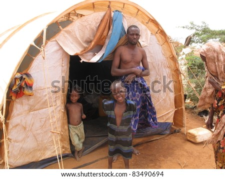 DADAAB, SOMALIA-AUGUST 15: An unidentified family lives in a tent in the Dadaab refugee camp where thousands of Somalis wait for help because of hunger on August 15, 2011 in Dadaab, Somalia. - stock photo
