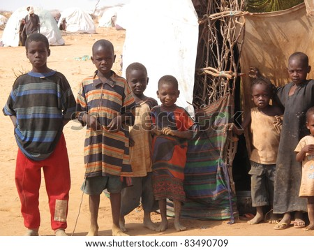DADAAB, SOMALIA-AUGUST 15: Unidentified children pose for photos where they live in the Dadaab refugee camp where thousands of Somalis wait for help because of hunger on August 15, 2011 in Dadaab, Somalia.. - stock photo