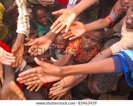 DADAAB, SOMALIA-AUGUST 15: Unidentified children stretch out their hands at the Dadaab refugee camp where thousands of Somalian wait for help because of hunger on August 15, 2011, in Dadaab, Somalia. - stock photo