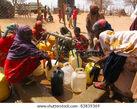DADAAB, SOMALIA-AUGUST 15: Unidentified men, women & children wait for relief aid in the Dadaab refugee camp where thousands of Somalis end up due to hunger on August 15, 2011 in Dadaab, Somalia. - stock photo